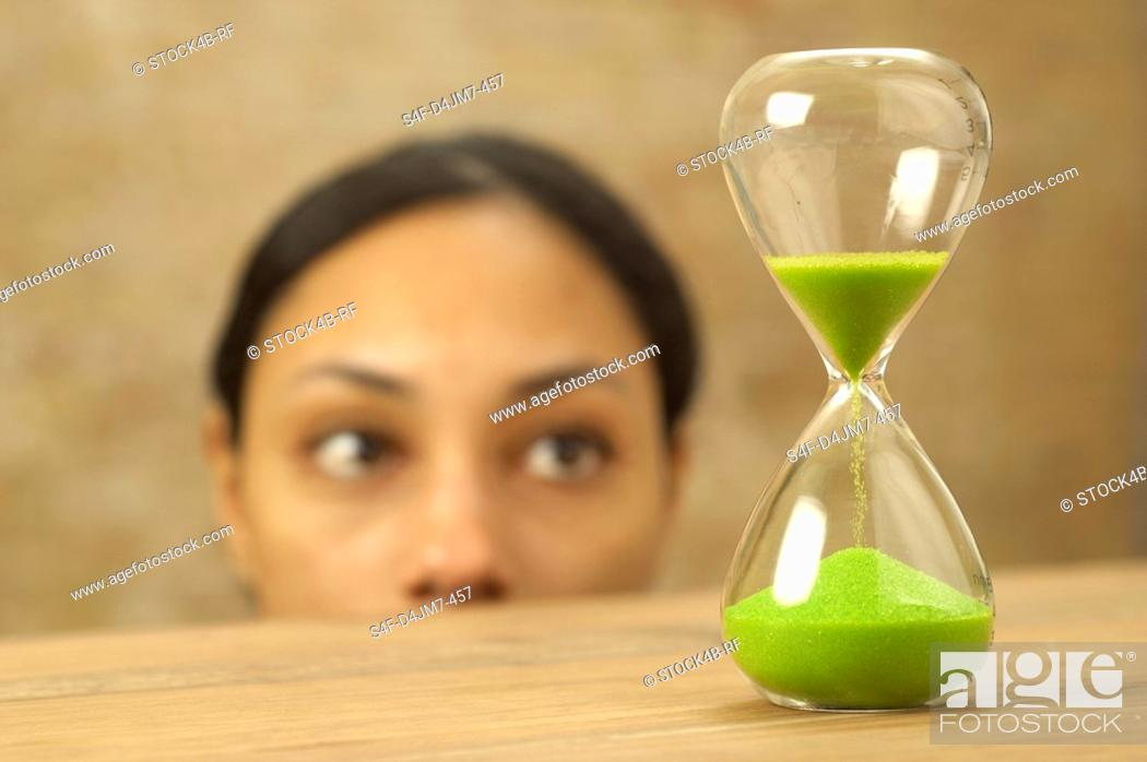 Stock Photo: Woman looking at hourglass with green sand.