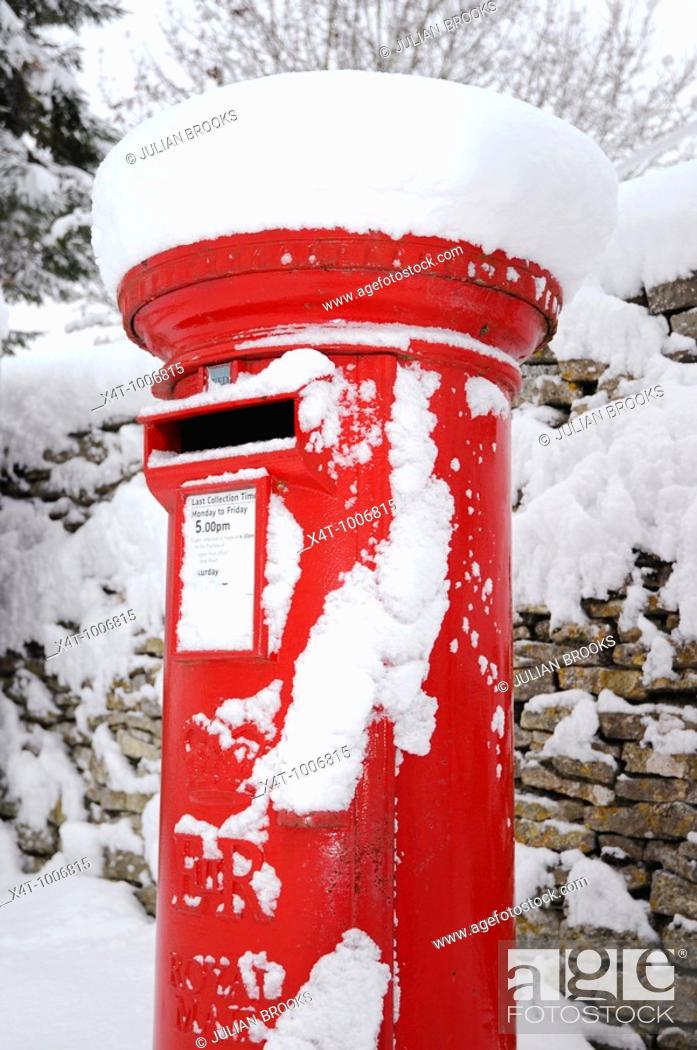 Stock Photo: A red pillar box in the snow in the cotswolds.