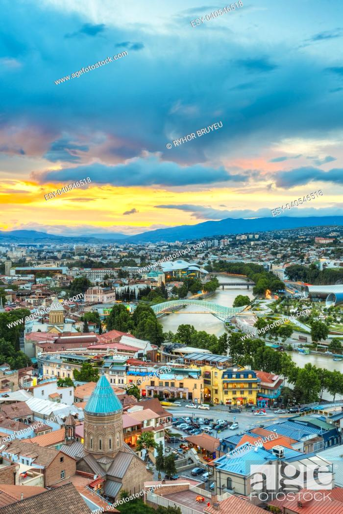 Stock Photo: The Top View Of Old Colorful Town And Kura Mtkvari River Under Bridges In Summer Tbilisi, Georgia Beautiful Scenic Sunset Sunrise Dawn Cloudy Sky Background.