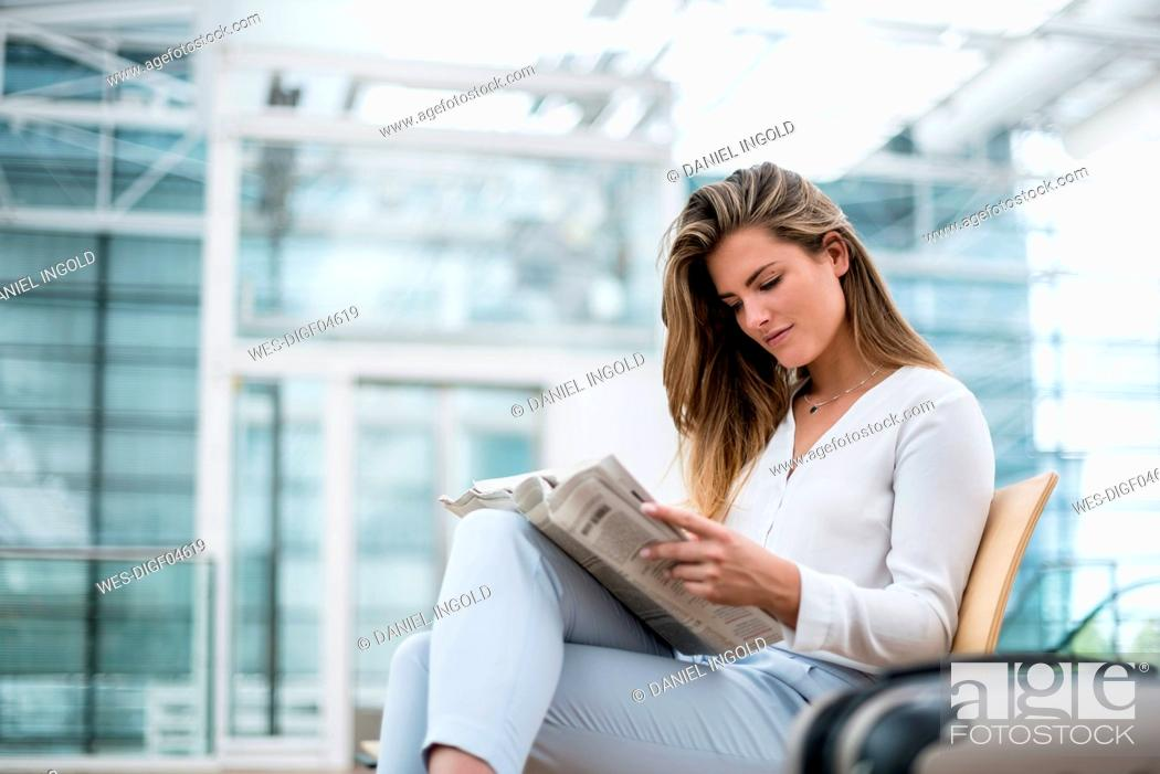 Stock Photo: Young businesswoman sitting outdoors with suitcase reading newspaper.