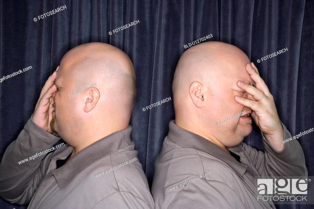 Stock Photo: Profile of bald identical twin men standing back to back and grimacing with hands to head.
