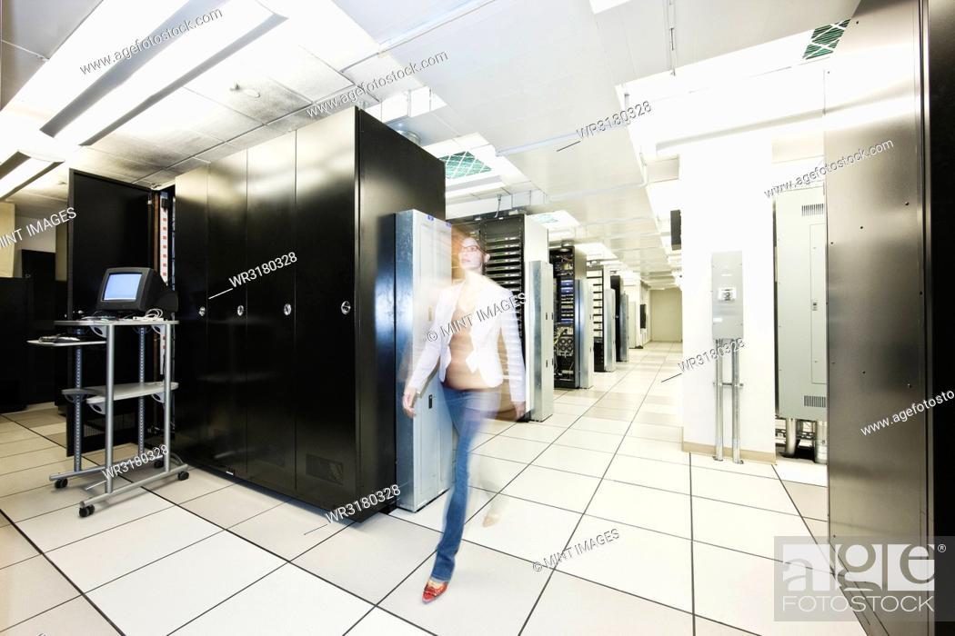 Photo de stock: Computer server room racks with technician in background.