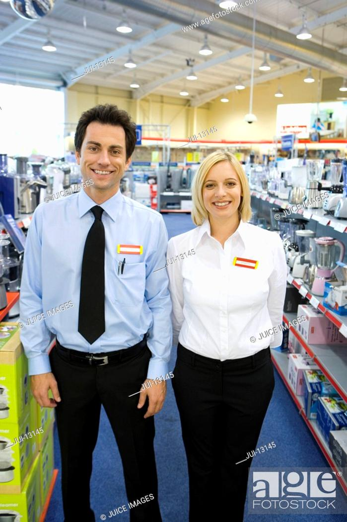 Stock Photo: Young salesman and woman in electronics aisle, smiling, porttrait.