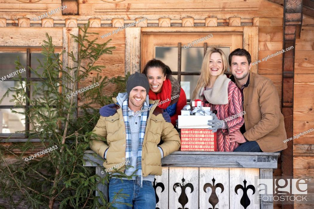 Stock Photo: Portrait of smiling couples with fresh cut Christmas tree and gifts in front of cabin.