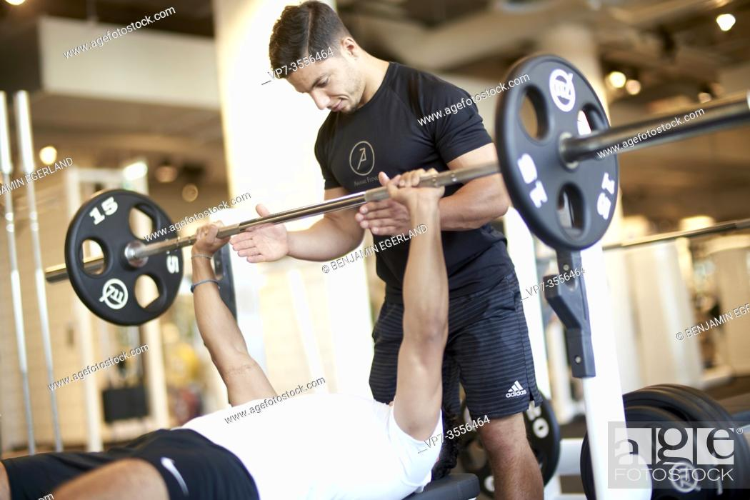 Stock Photo: Personal trainer assisting man lifting weights in gym.