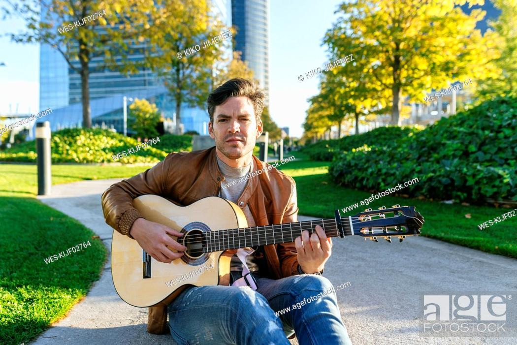 Imagen: Man playing guitar in an urban park, Madrid, Spain.