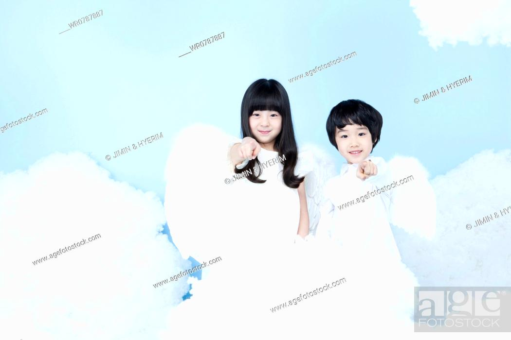 Stock Photo: two kids with looks of angels on the clouds.