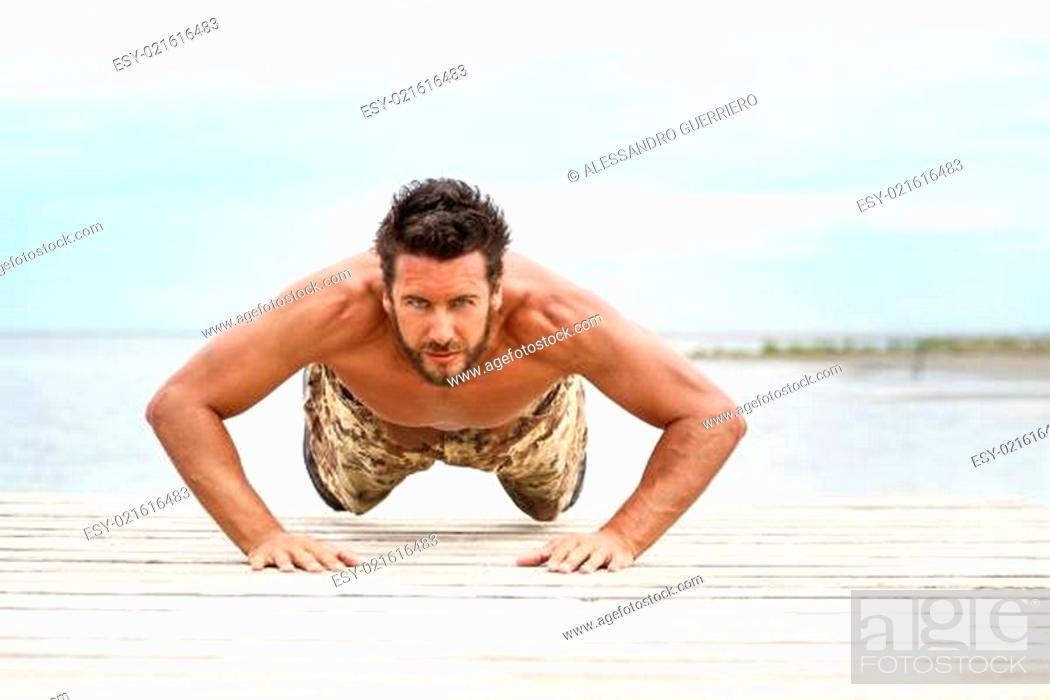 Stock Photo: Fit shirtless male fitness model in push up exercise.