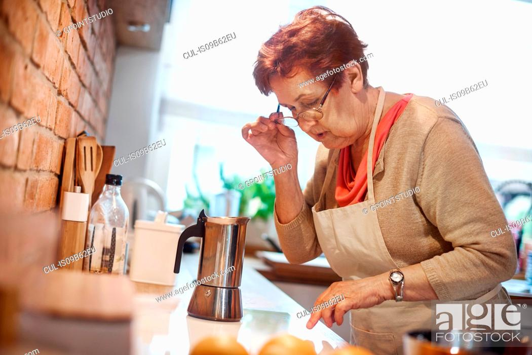 Stock Photo: Senior adult woman learning to use electric hob to make coffee.