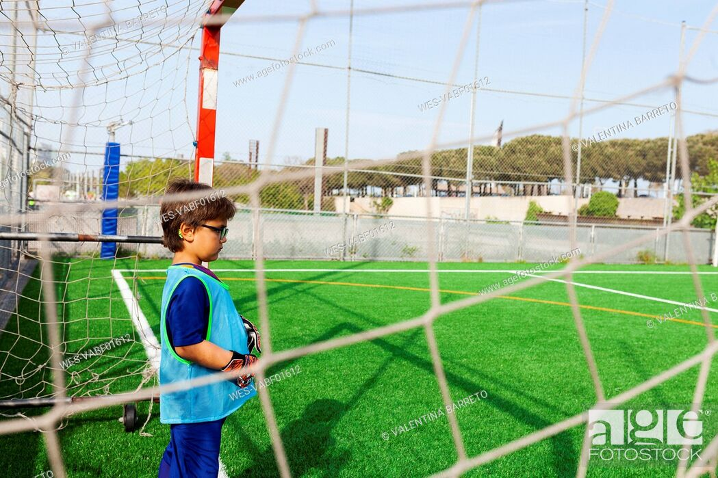 Stock Photo: Little boy standing at goal on football ground.