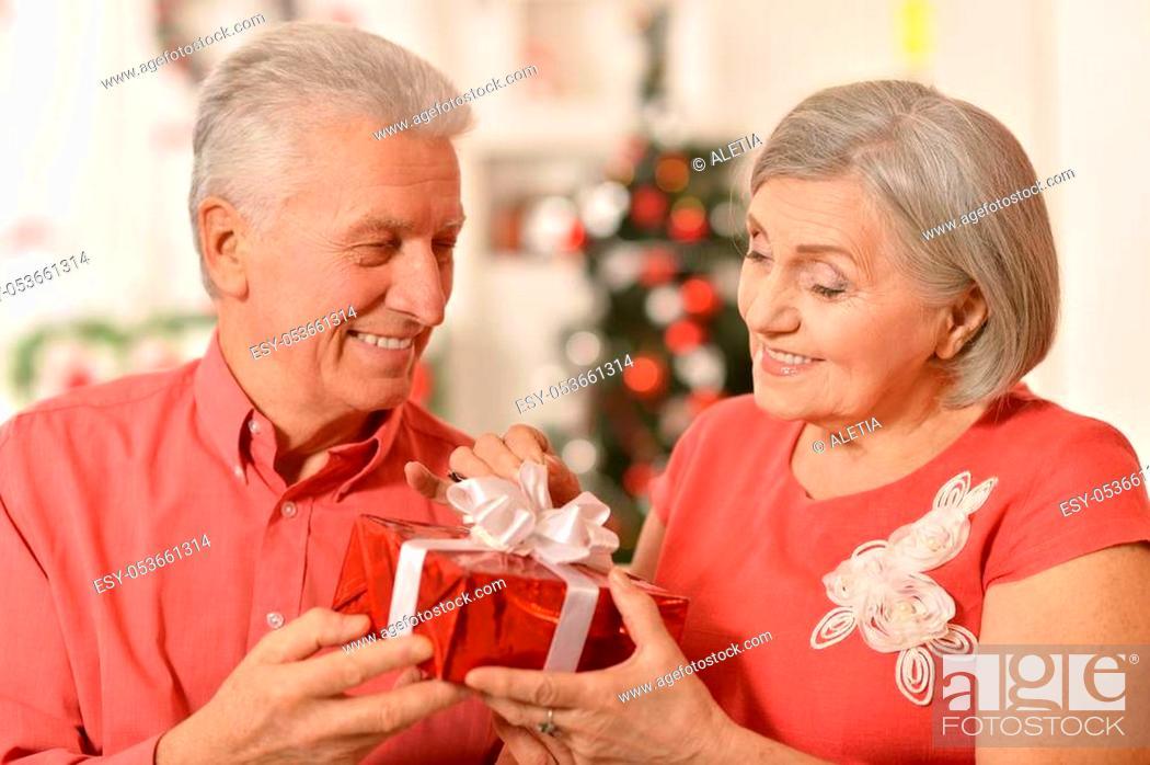 Stock Photo: Portrait of happy senior couple celibrating Christmas or New Year, holding gift box.