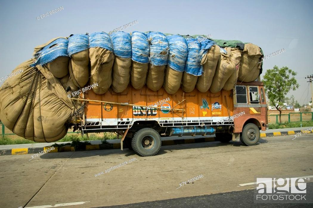 Stock Photo: A full truck goes down a road in India.