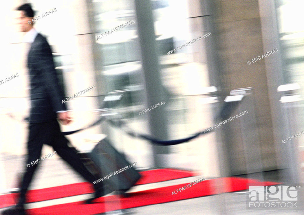 Stock Photo: Businessman walking with luggage, side view, blurred.