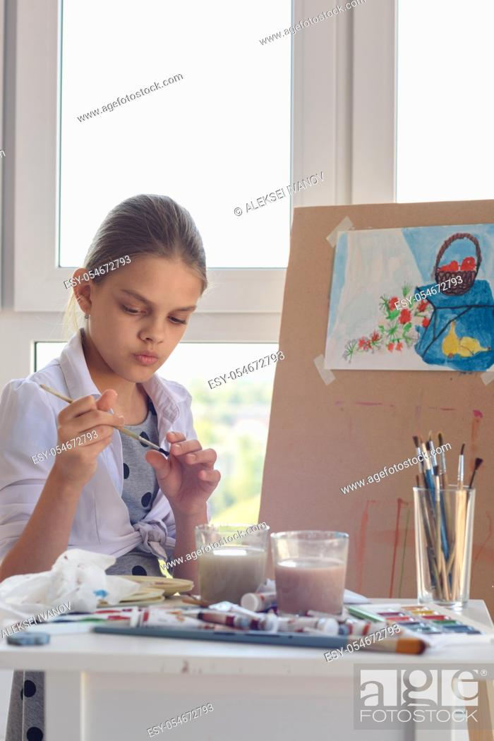 Stock Photo: Girl examines brush for drawing watercolor paints.