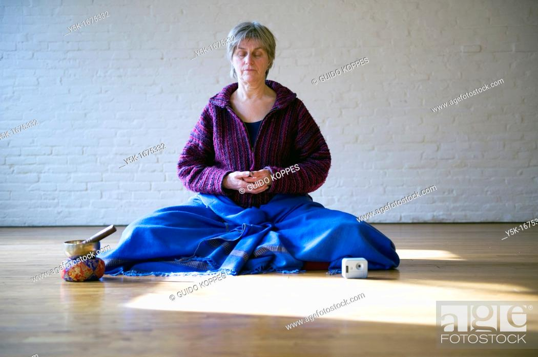 Stock Photo: Tilburg, Netherlands. Older woman, meditating in an empty room, using Buddhist techniques.