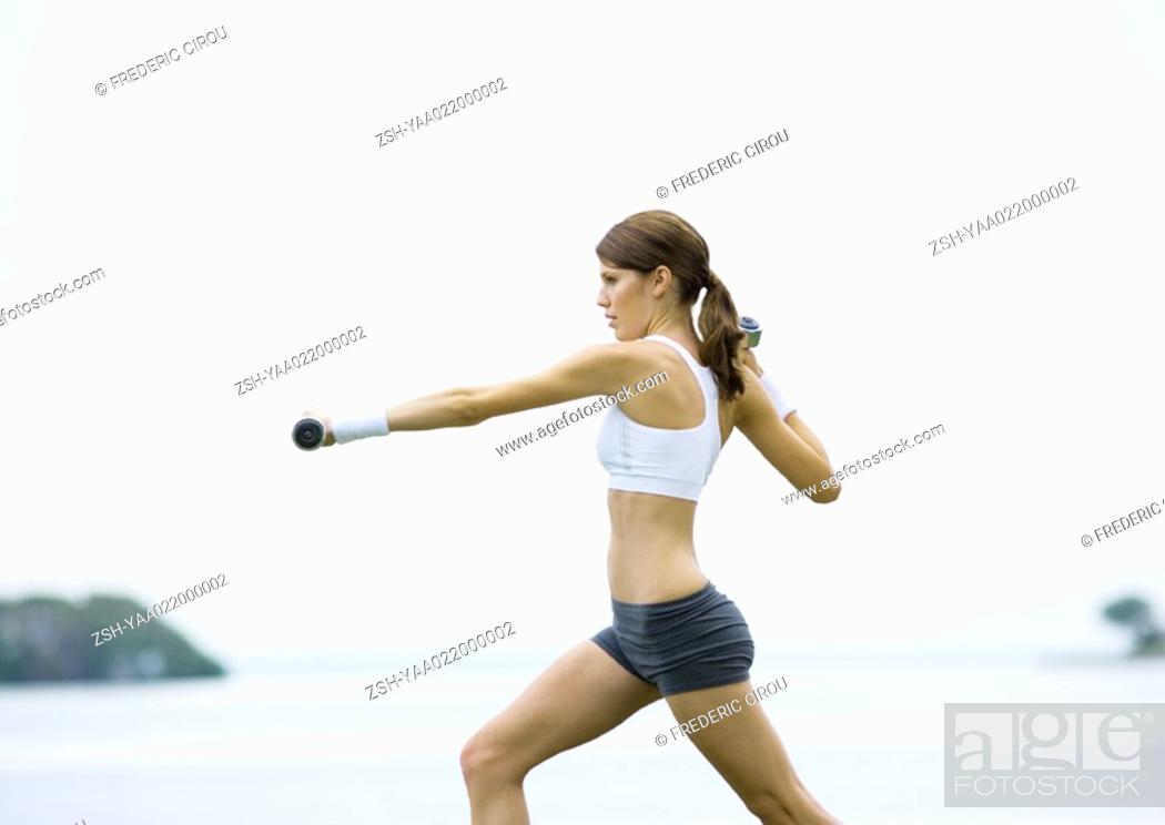 Stock Photo: Young woman working out with weights, outdoors.