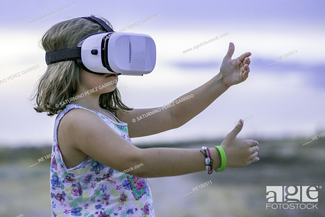 Stock Photo: Little girl playing with a virtual reality glasses.