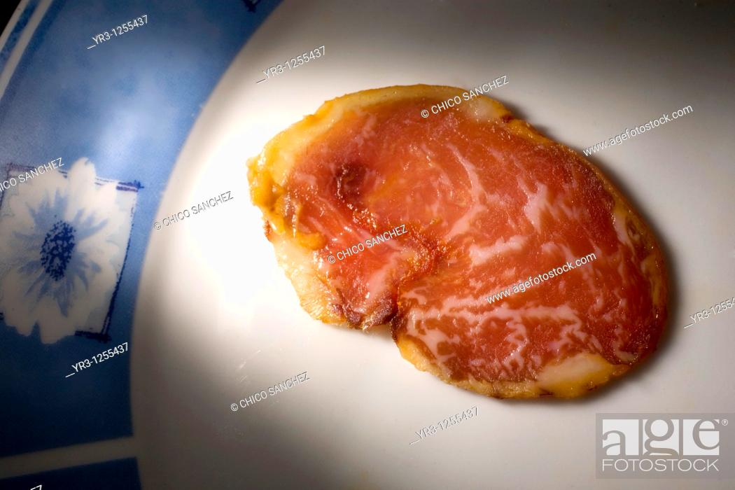 Stock Photo: A cured loin slice made from Spanish Iberian pigs, the source of Iberico ham known as pata negra, sits on a plate in Prado del Rey, Sierra de Cadiz.
