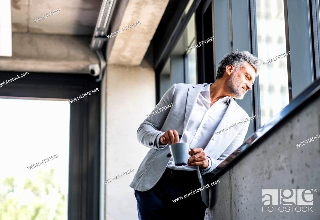 Stock Photo: Smiling mature businessman with coffee mug looking out of window.