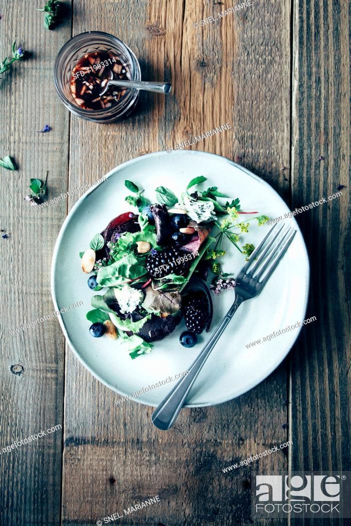 Stock Photo: Leaf salad with blueberries, blackberries, beetroot, edible flowers, roasted almonds and red wine vinegar & onion vinaigrette.