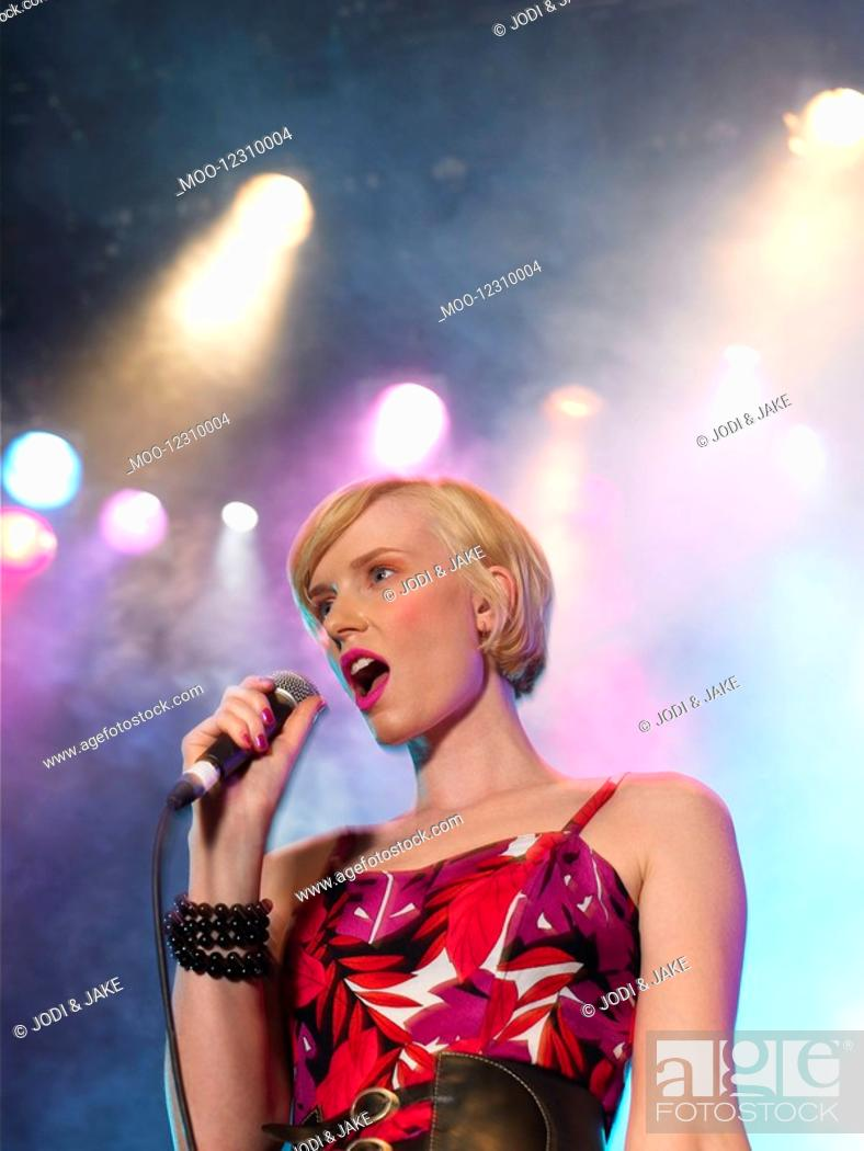 Stock Photo: Young Woman Singing in Concert on stage low angle view.