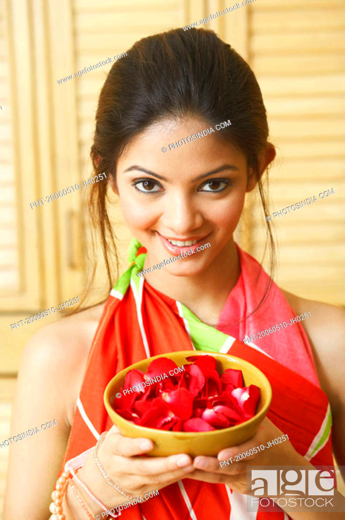 Stock Photo: Portrait of a young woman holding rose petals in a bowl.
