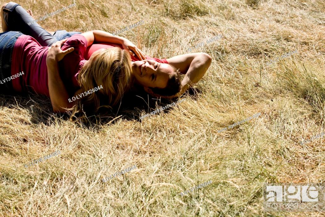 Stock Photo: A young couple lying on the grass, embracing.