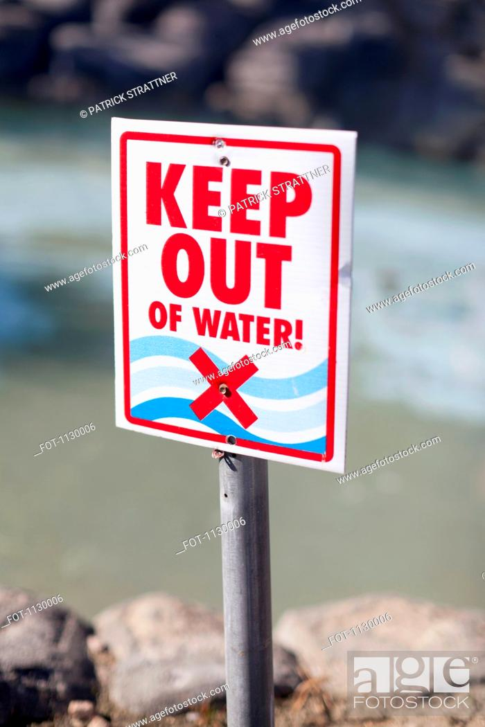 Stock Photo: A Keep Out of Water sign posted on a rocky beach.