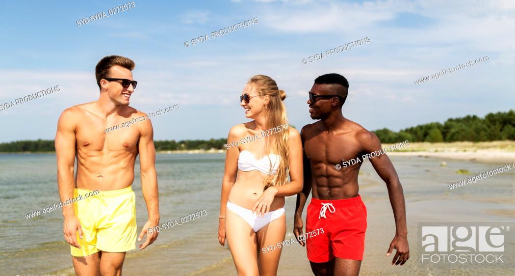 Stock Photo: happy friends walking along summer beach.