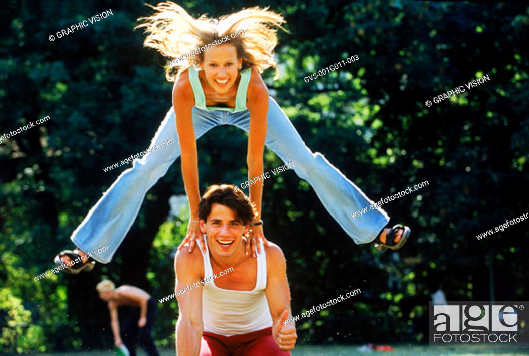 Stock Photo: Young woman hurdling over young man.