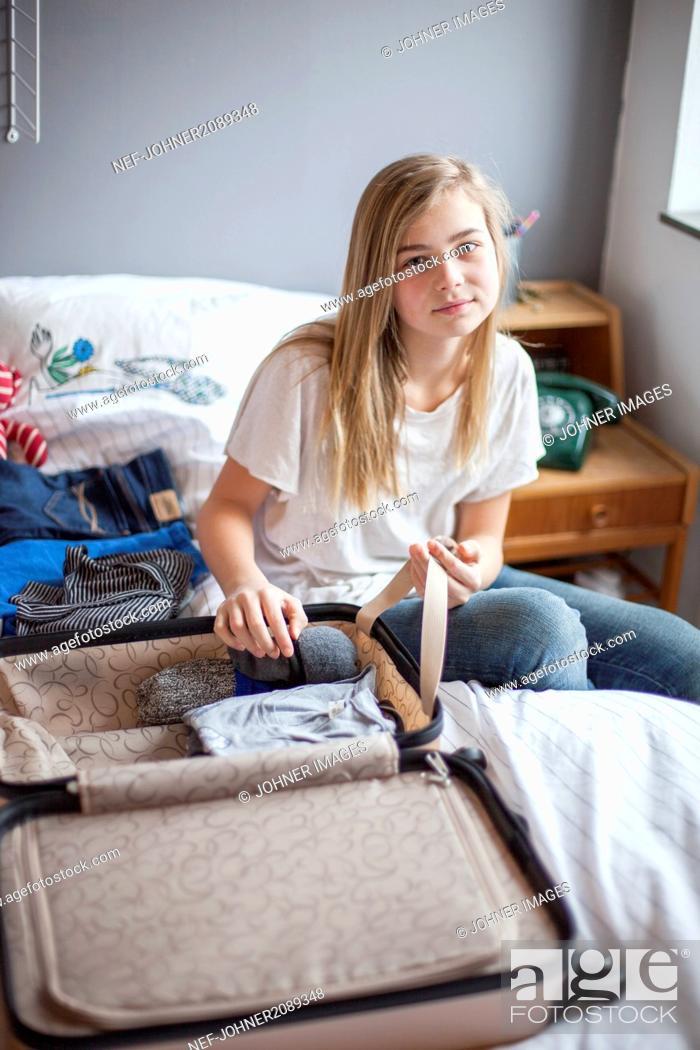 Stock Photo: Girl packing.