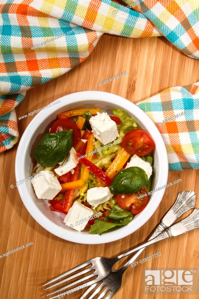 Imagen: mediterranean salad with red and yellow paprika stripes, goat cheese cubes, cherry tomatoes and basil in a bowl.