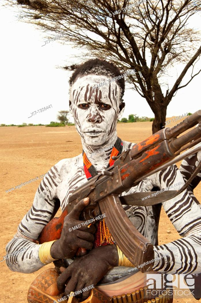 Stock Photo: Karo warrior with body and facial paintings holding a rifle, Omo river valley, Southern Ethiopia.