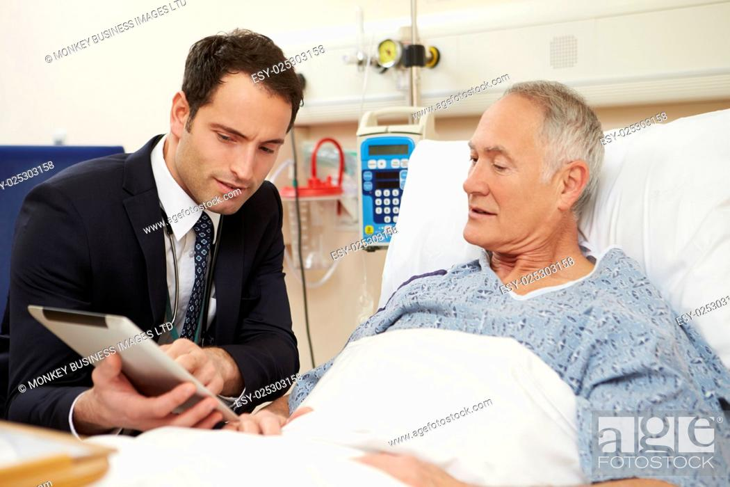 Stock Photo: Doctor Sitting By Male Patient's Bed Using Digital Tablet.