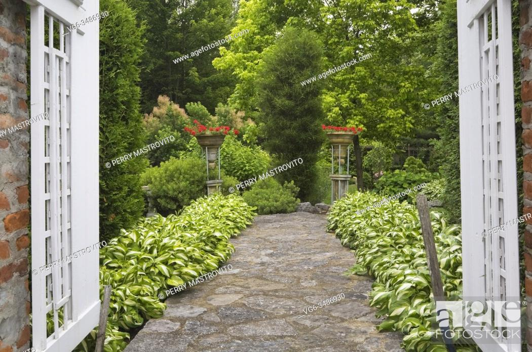 Stock Photo: Red brick columns with white wooden opened fence gate and flagstone path bordered by Hosta plants in private backyard formal garden in early summer, Quebec.
