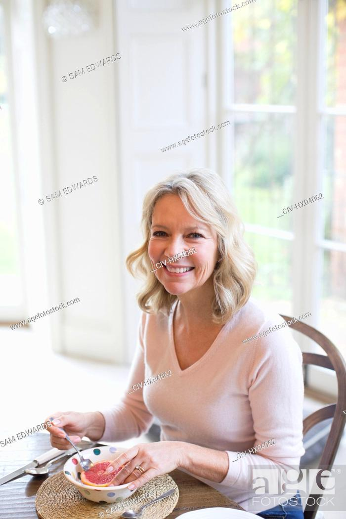 Stock Photo: Portrait smiling mature woman eating grapefruit.