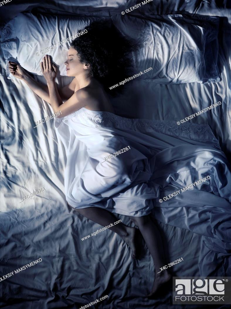 Stock Photo: Artistic photo of a young woman sleeping alone in bed on her side at night in dark bedroom lit by moonlight overhead view.