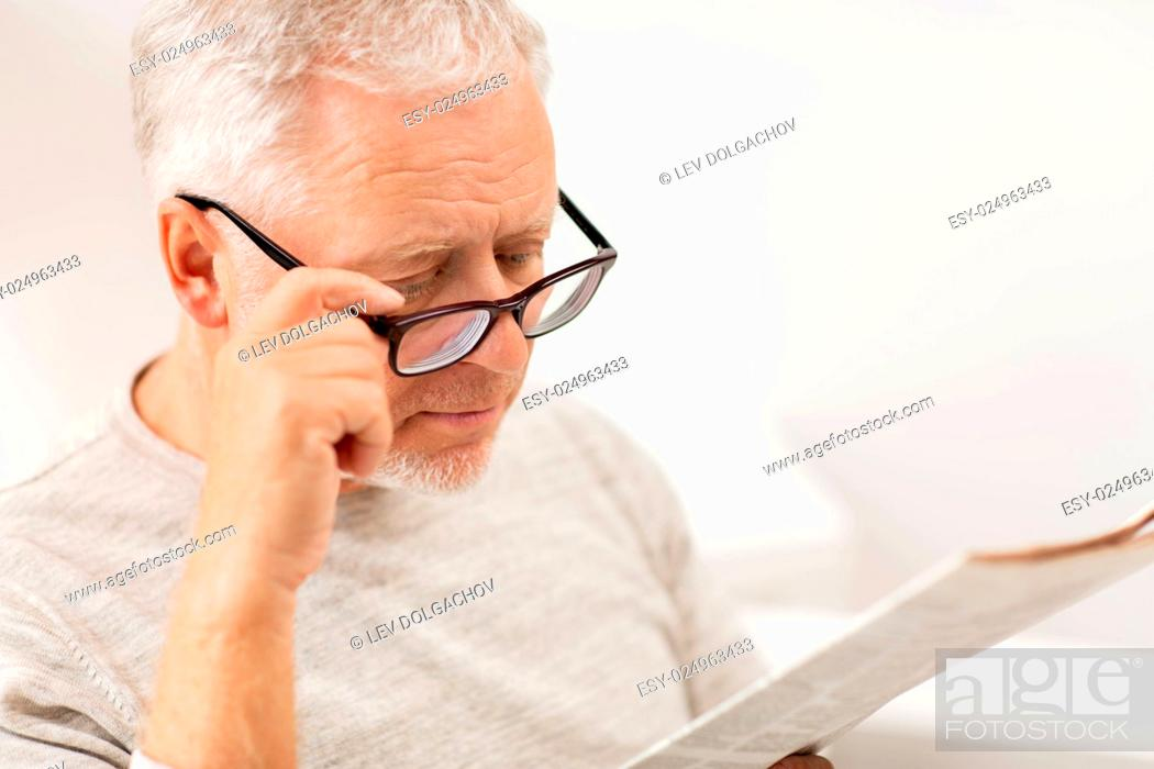 Stock Photo: leisure, information, people, vision and mass media concept - close up of senior man in glasses reading newspaper at home.
