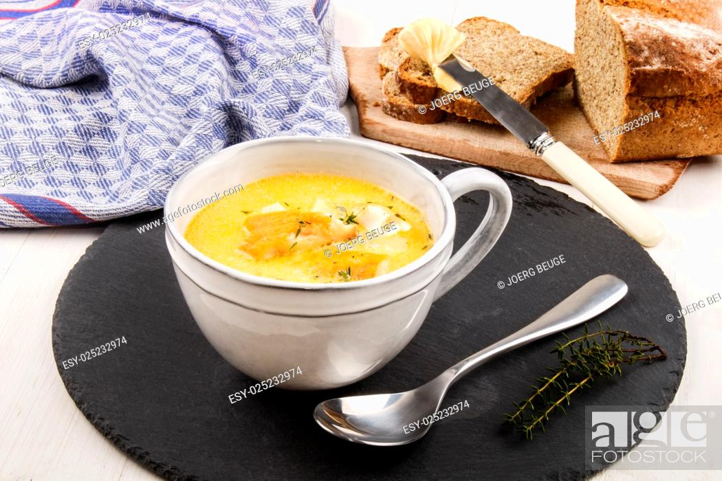 Stock Photo: specialty from scotland, freshly cooked cullen skink with thyme in a mug on slate.