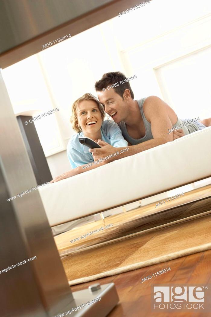 Stock Photo: Couple on bed watching television together.