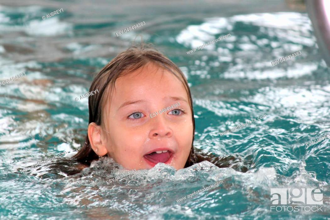 Stock Photo: Girl child frolicking in the shallow end of a pool.