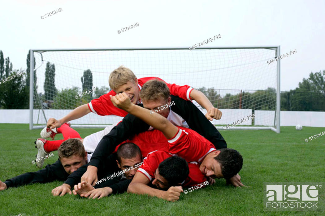 Stock Photo: Soccer players lying in a crowd on grass.