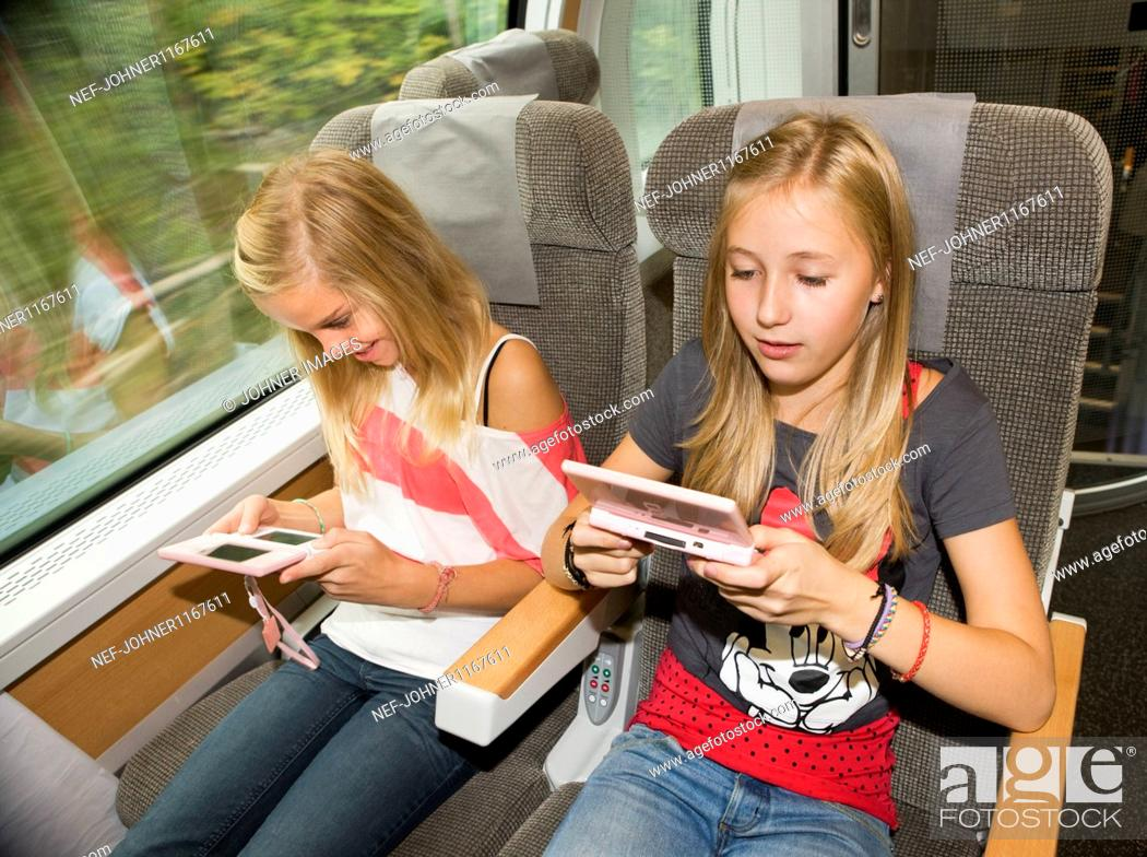 Stock Photo: Twin girls playing video games while traveling on high speed train.