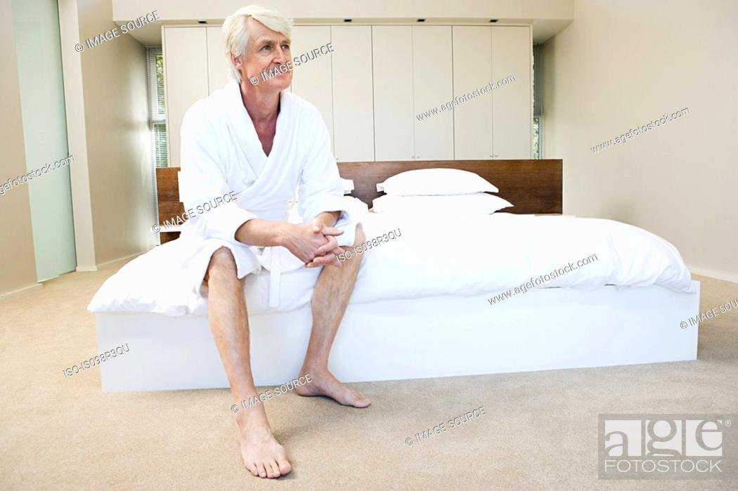 Stock Photo: Middle aged man in bathroom sitting on edge of bed.