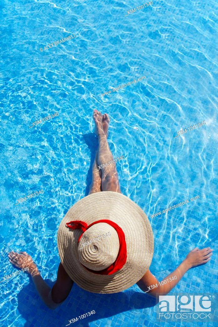 Stock Photo: Woman in a sun hat sunbathing in a blue swimming pool.