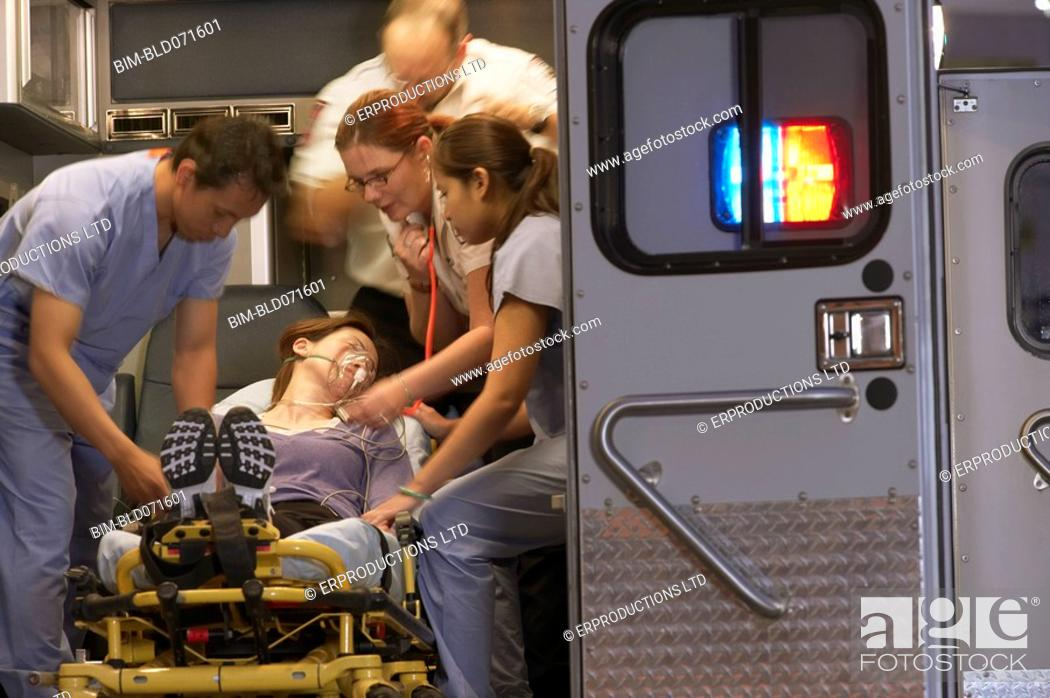 Stock Photo: Multi-ethnic medical professionals with patient in ambulance.