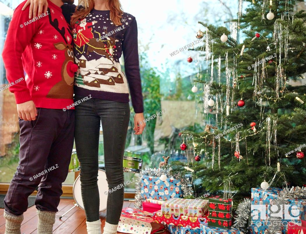 Stock Photo: Couple standing in front of Christmas tree wearing Christmas jumpers.
