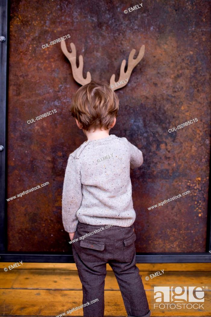 Stock Photo: Young boy standing facing wall, cardboard reindeer cut out on wall behind him.