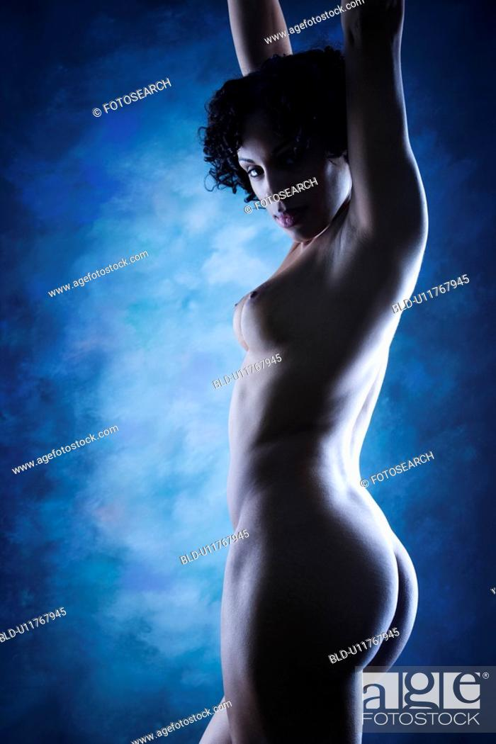 Stock Photo: Nude woman standing with arms raised.