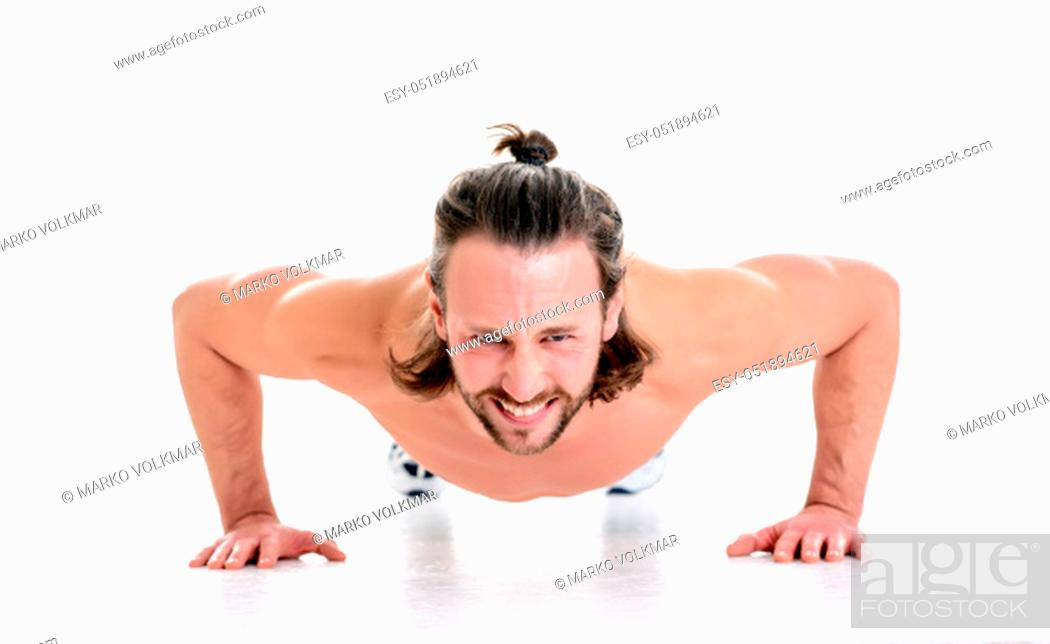 Stock Photo: young man doing press-up in front of white background.